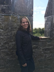 Woman posing next to battlement on Bunratty Castle